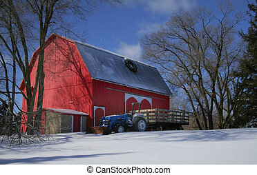 Blue tractor parked next to red barn in the farm