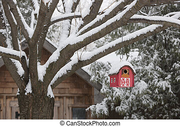 Red barn birdhouse on tree in winter