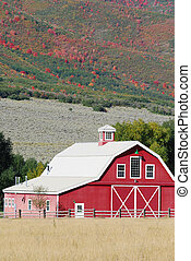 Large red barn with autumn colors on the mountains behind it.