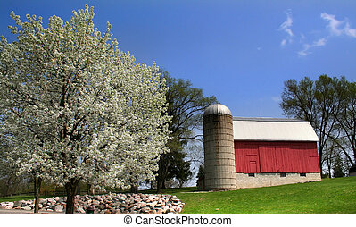 Red barn in the scenic spring time landscape of Michigan.