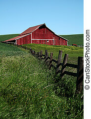 Red barn with fence leading to it, with brown horse in background