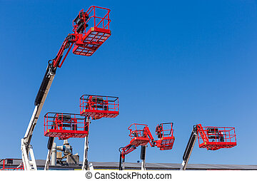 Red baskets on the booms of articulated boom lifts
