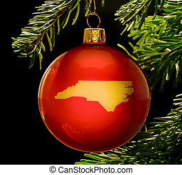 Red bauble with the golden shape of North Carolina hanging...