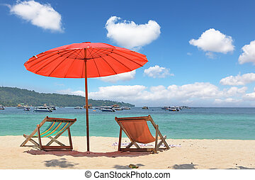 Red beach umbrella and deck chairs on the sand
