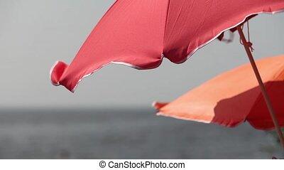 red beach umbrella against a blue sky close to