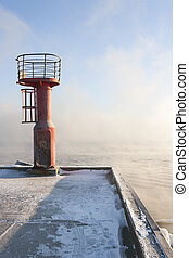 Red beacon at the end of a pier