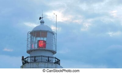 Red beacon light near the sea. Against the background of the morning sky in the clouds