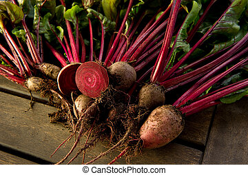 Fresh organic beets just picked from the garden shot on a wood table.