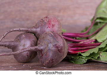 Red beets with tops on the wooden background
