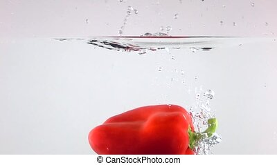 Red bell pepper falling down in water, light background super slow motion shot