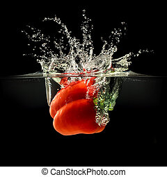 Red bell pepper falling in water with splash on black background