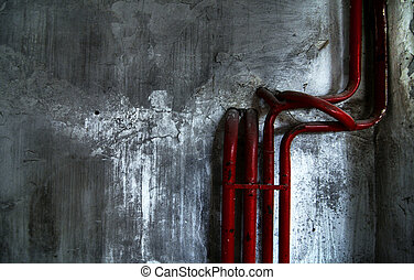 Red bent pipes on concrete walls