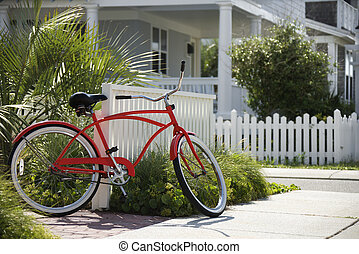 Red bicycle in front of house.