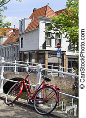 Red bicycle near a canal in Delft