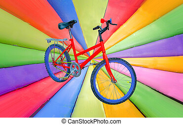 Red bicycle on grunge multicolored stripes