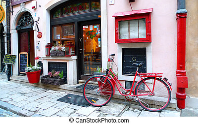 Red Bicycle parked on the street, at the door of a ...