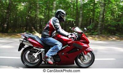 Red bike moves on asphalt road. Moving camera