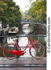 Red bike on a bridge in Amsterdam