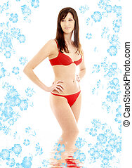 red bikini brunette in water with flowers