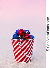 Red, Blue and White Balls Collected in Striped Bucket at Sunset for the Christmas Decor