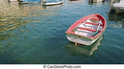 Red boat anchored at the sea port. A small fishing boat. ...