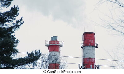 Red boiler house chimney. Steam against cloudy sky. Industrial zone of the city