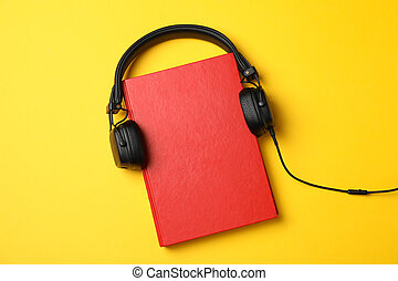 Red book with headphones on yellow background, top view