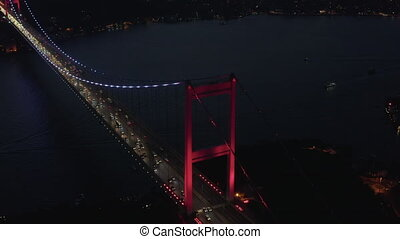 Red Bosphorus Bridge in Istanbul at Night with Car traffic into the City, Establishing Aerial backwards tilt up