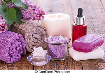 Red bottle with aromatic oil, burning candle, bowl with sea salt, soap, lilac flowers and towels.