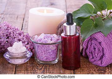 Red bottle with aromatic oil, burning candle, bowls with sea salt, lilac flowers and towels.