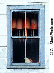 Red bouys haning inside an old window