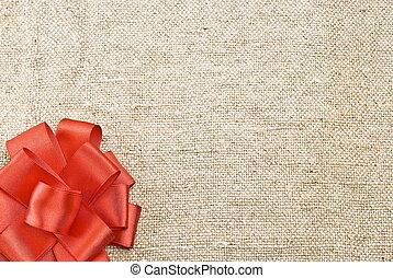 Red bow on sackcloth background
