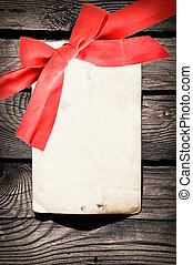 Red bow with card on old wood background