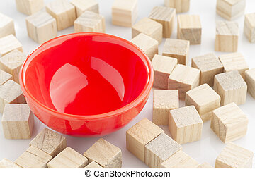 red bowl surrounded by wooden blocks on white background