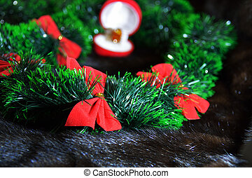 red bows in the green garlsnd in front of the open box with a ring