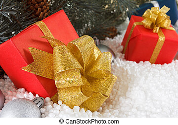 Red boxes with gold ribbon in snow under pine tree