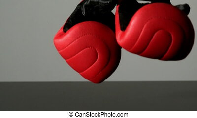 Red boxing gloves falling on black surface in slow motion