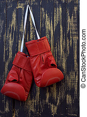 red boxing gloves hanging on a nail