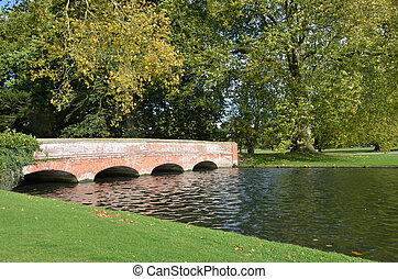 Red brick bridge in formal garden