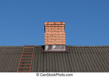 red brick chimney against blue sky
