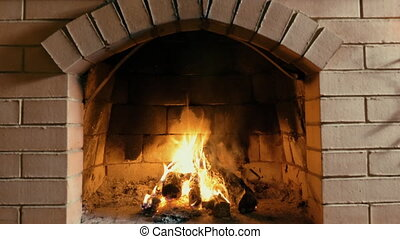Red brick fireplace with burning fire