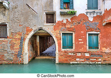 Red brick house on small canal in Venice, Italy.
