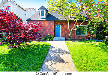 Red brick house with tile roof and maple tree in the front yard