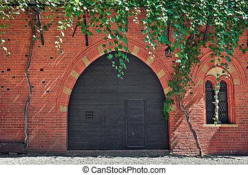 Red brick house with wooden door in Italy.