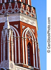 Red brick tower with white carved stone in gothic style