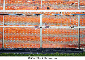 Red brick wall background with green grass