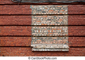 Red brick wall. The window is covered with bricks in the old house.