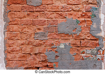 Red brick wall with peeling plaster as background, texture