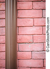 Red brick wall with pipe
