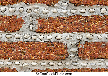 Red brick wall with small white rocks.